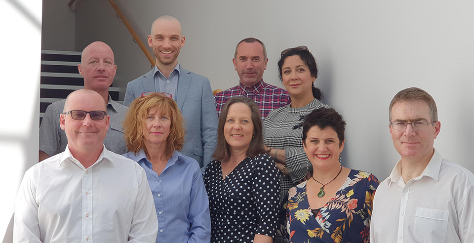 A team photograph of the current staff at the Christchurch office of Pedersen Read. They are standing in a well-lit stairwell with very light grey or white walls.